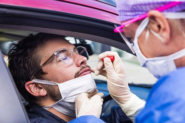 Healthcare professional taking a nasal swab from a patient for the COVID-19 RT-PCR Test